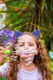 Petite fille bouclée heureuse jouant avec des bulles de savon sur une nature d'été, port oreilles bleues des accessoires de tigre Images stock
