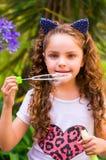 Petite fille bouclée heureuse jouant avec des bulles de savon sur une nature d'été, port oreilles bleues des accessoires de tigre Image libre de droits