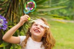 Petite fille bouclée heureuse jouant avec des bulles de savon sur une nature d'été, portant une robe et une fleur roses dans sa t Images stock