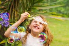 Petite fille bouclée heureuse jouant avec des bulles de savon sur une nature d'été, portant une robe et une fleur roses dans sa t Photos stock