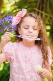 Petite fille bouclée heureuse jouant avec des bulles de savon sur une nature d'été, portant une robe et une fleur roses dans sa t Image libre de droits