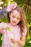 Petite fille bouclée heureuse jouant avec des bulles de savon sur une nature d'été, portant une robe et une fleur roses dans sa t Photographie stock libre de droits
