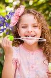 Petite fille bouclée heureuse jouant avec des bulles de savon sur une nature d'été, portant une robe et une fleur roses dans sa t Photo stock