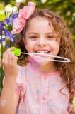 Petite fille bouclée heureuse jouant avec des bulles de savon sur une nature d'été, portant une robe et une fleur roses dans sa t Photographie stock