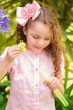 Petite fille bouclée heureuse jouant avec des bulles de savon sur une nature d'été, portant une robe et une fleur roses dans sa t Photos libres de droits