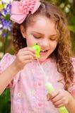 Petite fille bouclée heureuse jouant avec des bulles de savon sur une nature d'été, portant une robe et une fleur roses dans sa t Images libres de droits