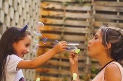 Petite fille bouclée heureuse jouant avec des bulles de savon sur une nature d'été avec sa maman, à un arrière-plan brouillé Photo stock