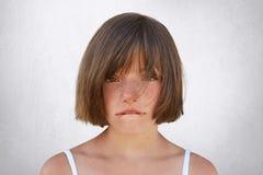 Petite fille bouleversée ayant la querelle avec ses parents, regardant innocent dans l'appareil-photo tout en courbant ses lèvres image stock