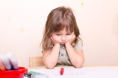 Petite fille bouleversée s'asseyant au bureau à l'école Photos libres de droits
