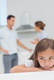 Petite fille bouleversée écoutant les parents qui discutent Photographie stock libre de droits