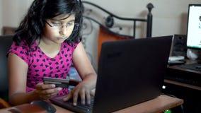 Petite fille branchée faisant des achats de paiement en ligne sur Internet à l'aide d'une carte de crédit ou de carte de débit en banque de vidéos