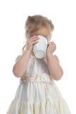 Petite fille buvant de la cuvette blanche Photo stock