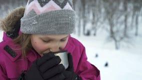 Petite fille buvant la boisson chaude dehors en hiver banque de vidéos