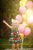 Petite fille caucasienne blonde heureuse dehors avec des ballons images libres de droits