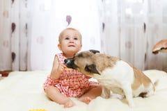 Petite fille caucasienne drôle que l'enfant se repose à la maison sur le plancher sur un tapis léger avec le meilleur ami du chie Images libres de droits