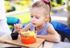 Petite fille caucasienne mangeant des fritures de rench avec de la sauce au café de rue dehors photo libre de droits