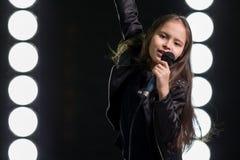Petite fille chantant devant des lumières d'étape Photo libre de droits