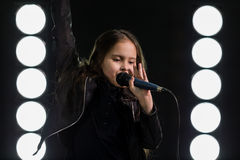 Petite fille chantant devant des lumières d'étape Image libre de droits