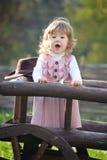 Petite fille chantant près de la frontière de sécurité en bois Images stock