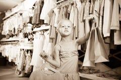 Petite fille chez la boutique de vêtements des enfants Photo stock