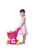 Petite fille chinoise asiatique avec le chariot à achats complètement du vegetabl Image libre de droits