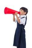 Petite fille chinoise asiatique d'école primaire tenant le rétro mégaphone Image libre de droits