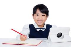 Petite fille chinoise asiatique dans l'uniforme étudiant avec le comput de comprimé images stock
