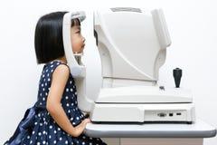 Petite fille chinoise asiatique faisant l'examen de yeux par automatique au sujet de Images libres de droits