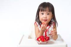 Petite fille chinoise asiatique mangeant des fraises Images stock