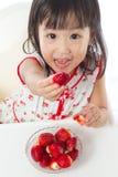 Petite fille chinoise asiatique mangeant des fraises Photographie stock libre de droits