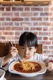 Petite fille chinoise asiatique mangeant des spaghetti Bolonais Images libres de droits