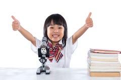 Petite fille chinoise asiatique montrant des pouces avec le microscope images libres de droits