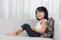Petite fille chinoise asiatique se trouvant sur le sofa avec le téléphone Image libre de droits