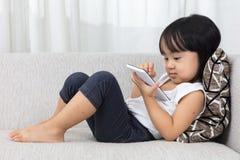 Petite fille chinoise asiatique se trouvant sur le sofa avec le téléphone Photographie stock libre de droits