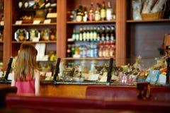 Petite fille choisissant des bonbons dans une boutique de bonbons au chocolat Images libres de droits