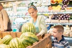 Petite fille choisissant des grenades dans un magasin de nourriture ou un supermarché images stock