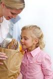 Petite fille éclatant le sac d'épicerie avec sa mère Photographie stock libre de droits