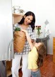 Petite fille éclatant le sac d'épicerie avec sa mère Photos libres de droits