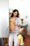 Petite fille éclatant le sac d'épicerie avec sa mère Photo stock