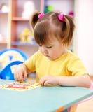 Petite fille colorant une illustration dans l'école maternelle Photo libre de droits