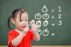 Petite fille comptant son doigt Photo stock