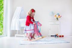 Petite fille conduisant un cheval de jouet Photos libres de droits