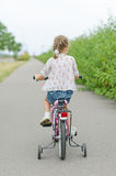 Petite fille conduisant une bicyclette Images stock