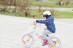 Petite fille conduisant une bicyclette Photographie stock libre de droits