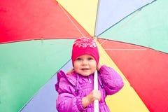 petite fille contre un parapluie de couleur images stock