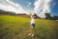 Petite fille courant avec le cerf-volant heureux et souriant sur le champ d'été Images libres de droits