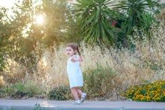 Petite fille courant dehors avec le coucher du soleil image stock
