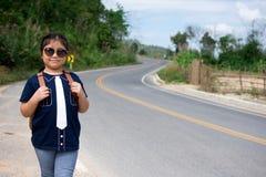 Petite fille courant loin sur la route en avant Photographie stock libre de droits