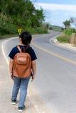 Petite fille courant loin sur la route en avant Photo stock
