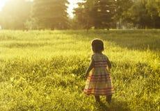 Petite fille courant sur le pré avec le coucher du soleil Photo stock